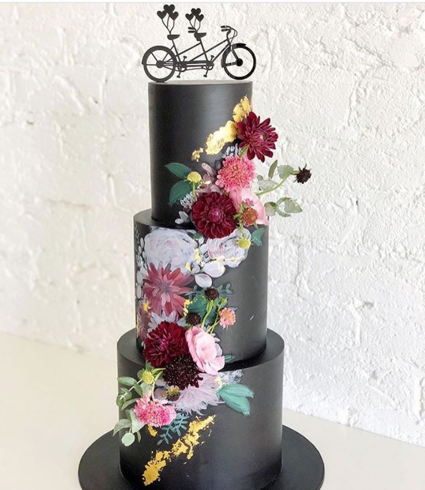 Black cake with florals painted & attached by @ivyandstonecakedesign