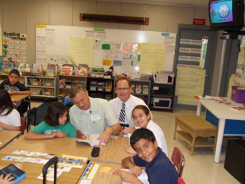 Adam and fellow Rotarian giving out dictionaries to the 3rd grade classes at Calusa Elementary School.