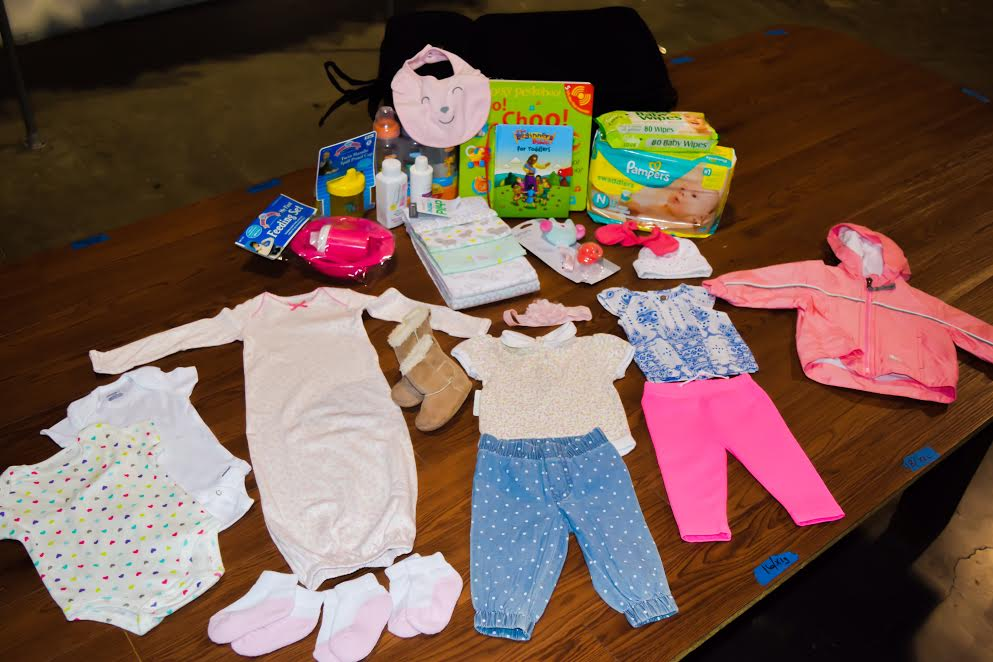 Newborn kits include: Duffel bag, 2 shirts, 2 pants, 2 onesies, pajamas, 3 pairs of socks, jacket/winter coat,mittens, hat, blanket,Beginner's Bible, book, package of diapers, package of wipes, a diaper bag filled with lotion, powder, soap, & bottles, + seasonal items (hoodie/jacket during Spring & Fall, coat during Winter).
