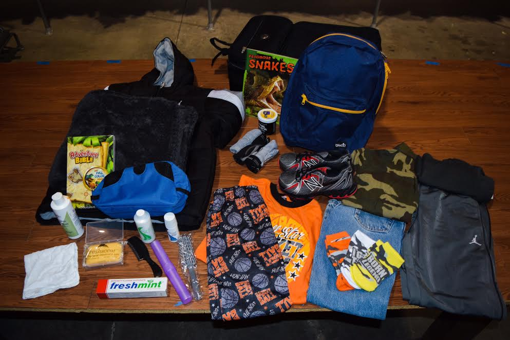Elementary age kits include: Duffle bag, 2 shirts, 2 pants, pajamas, 3 pairs of socks, 3 pairs of underwear, pair of shoes, Adventure Bible, backpack (with school supplies), hygiene kit (shampoo, conditioner, toothbrush, toothpaste, soap,comb,& ethnic hair care product if requested), blanket,book, stuffed animal + seasonal items (hoodie/jacket during Fall & Spring, coat during Winter, swimsuit during Summer).
