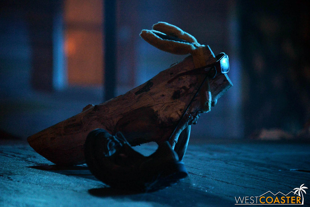 Log Bunny started one year when crews were clearing brush around the backlot area and found a log with a pair of truncated branches sticking out, resembling legs.  It was unique and thus kept.  Later, during Horror Nights, the staff realized that a common fashion accessory lost during the commotion of the Terror Tram was bunny ears, so an employee stuck a pair on the log, and thus, Log Bunny was born.
