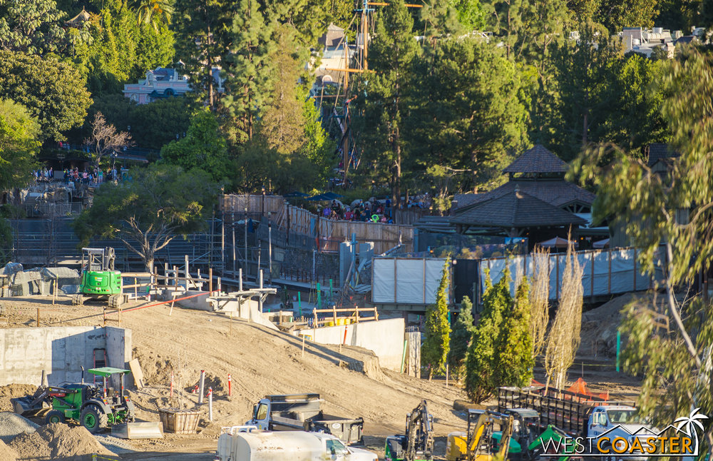 "It would appear that the bridge/pathway to the left of the tarp that currently shields the view of Hungry Bear diners from the drained Rivers of America will slowly ramp down and then turn and duck below the railroad tracks before reappearing up and into ""Star Wars"" Land, similar to who guests currently access Mickey's Toontown from Fantasyland (but with a kink).  This might introduce a pinchpoint at this part of the river just downstream of the Davy Crockett Canoe station compared to the previous iteration, but there's still plenty of room for the canoes and riverboats."