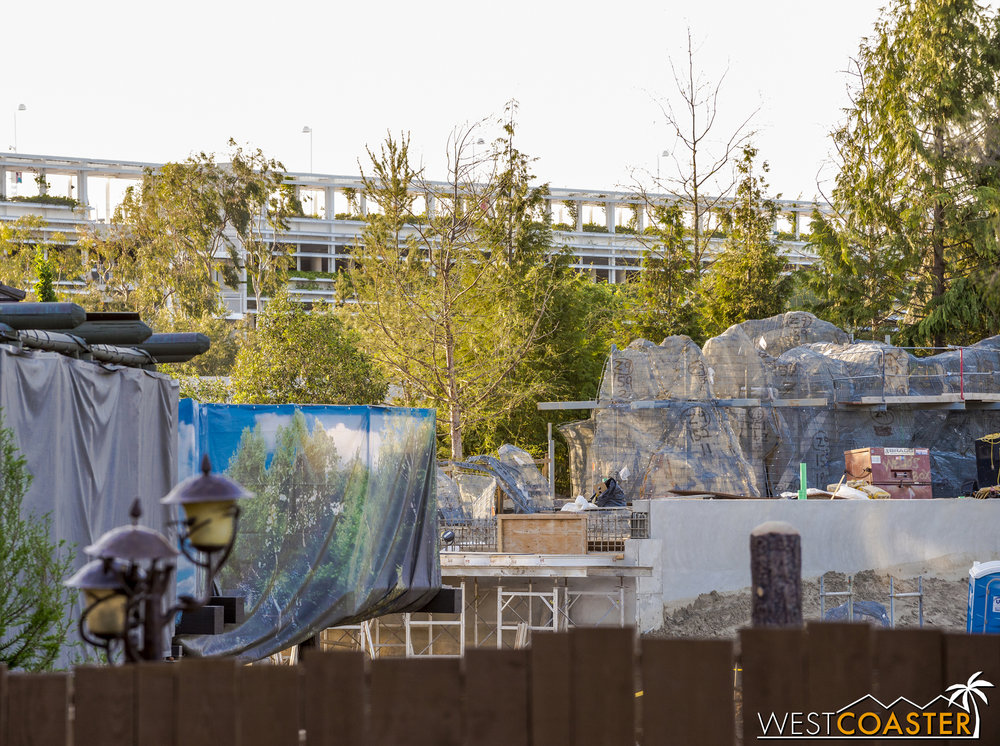 "Screening of the Hungry Bear beyond.  You can't see it because the wall is blocking it, but when facing the Hungry Bear signage and entrance, there will be a pathway just to the right that ramps downward to the river and ambles along before ducking under the Disneyland Railroad and entering ""Star Wars"" Land"