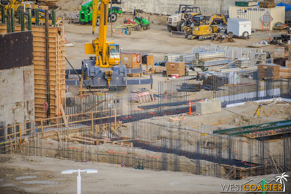 All of this is happening right adjacent to the no-longer-pit area.  What you see is steel reinforcing bars for strip footings and concrete walls.  The orange caps are for rebar that ends at chest or waist level compared to grade or lower, to prevent impalement in case anyone accidentally trips and falls.