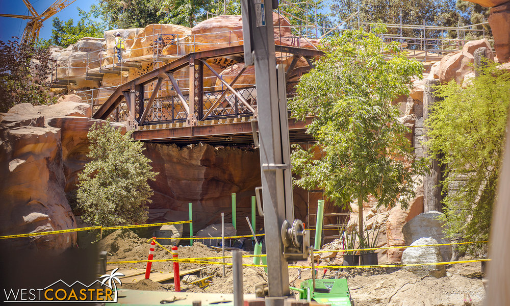 A peek between the slots reveals this: another arch bridge over which the Disneyland Railroad will run.