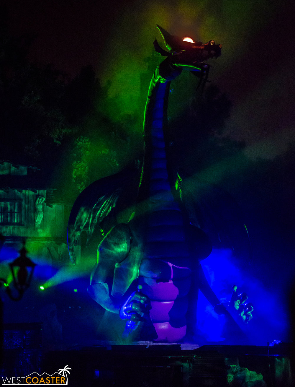 As you can see, however now, the dragon's eyes are lit as the beast rises out of its underground lair.  One might argue that having ol' Murphy (as the dragon is nicknamed by fans) slowly come out of the shadows and fog is actually more dramatic, but if that was the case, the projections showing dragon Maleficent should have been changed.