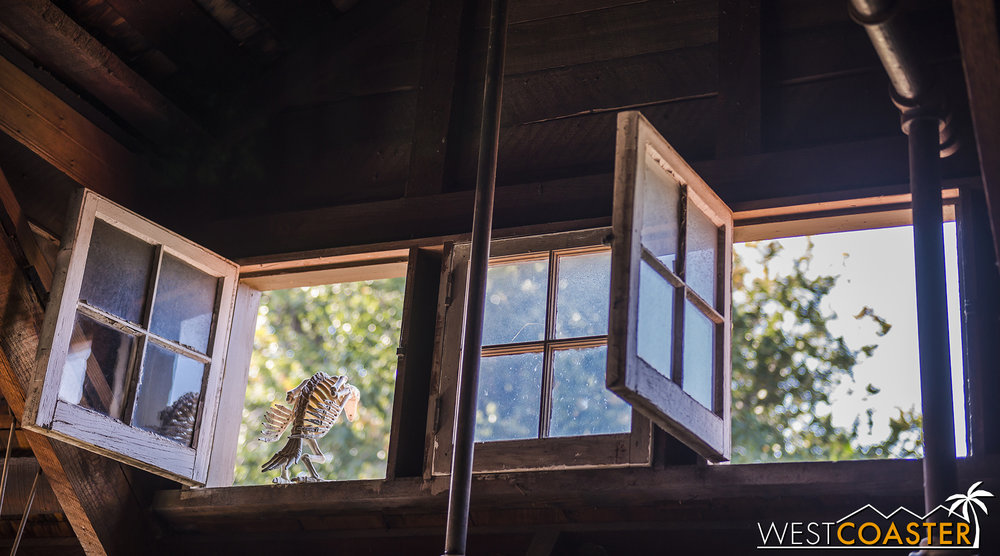 A skeletal bird perches on an open window in the loft.