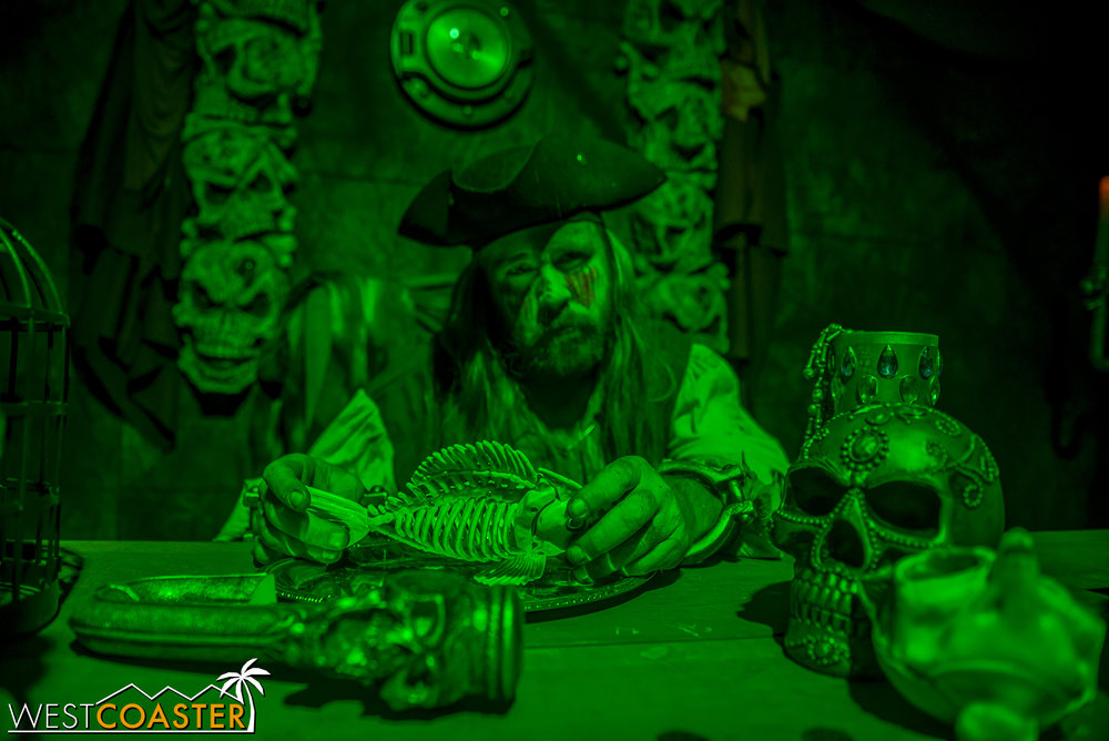 A pirate inspects a dead fish inside The Damned.