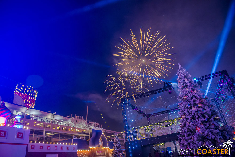 Fireworks are set off behind the rear of the ship.