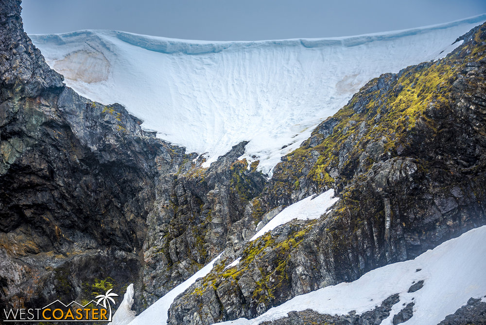 What seems to be a wave of ice cresting over the mountains and rocks.