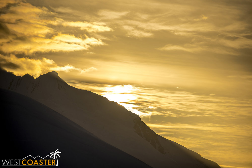 The radiant setting sun behind an unamed Antarctic mountain.