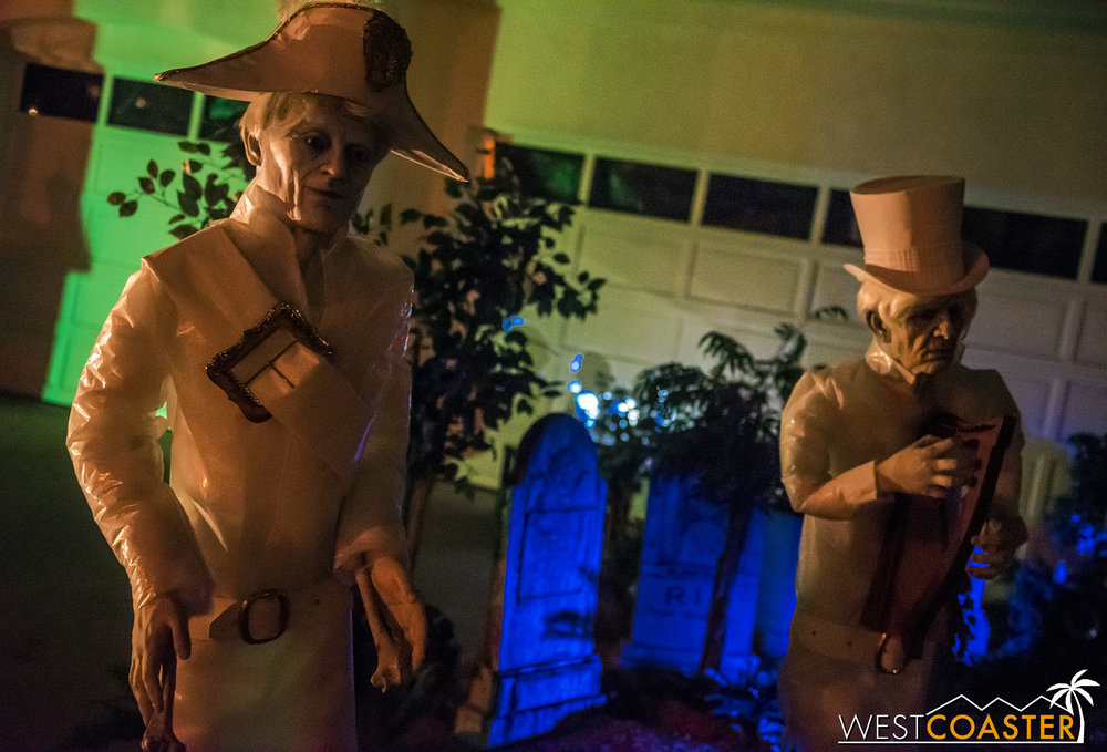 Ghostly figures stand outside the Haunted Mansion Haunt.