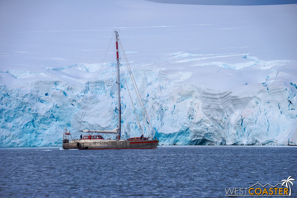 A sailboat in the distance, in front of a heavy blanket of ice.