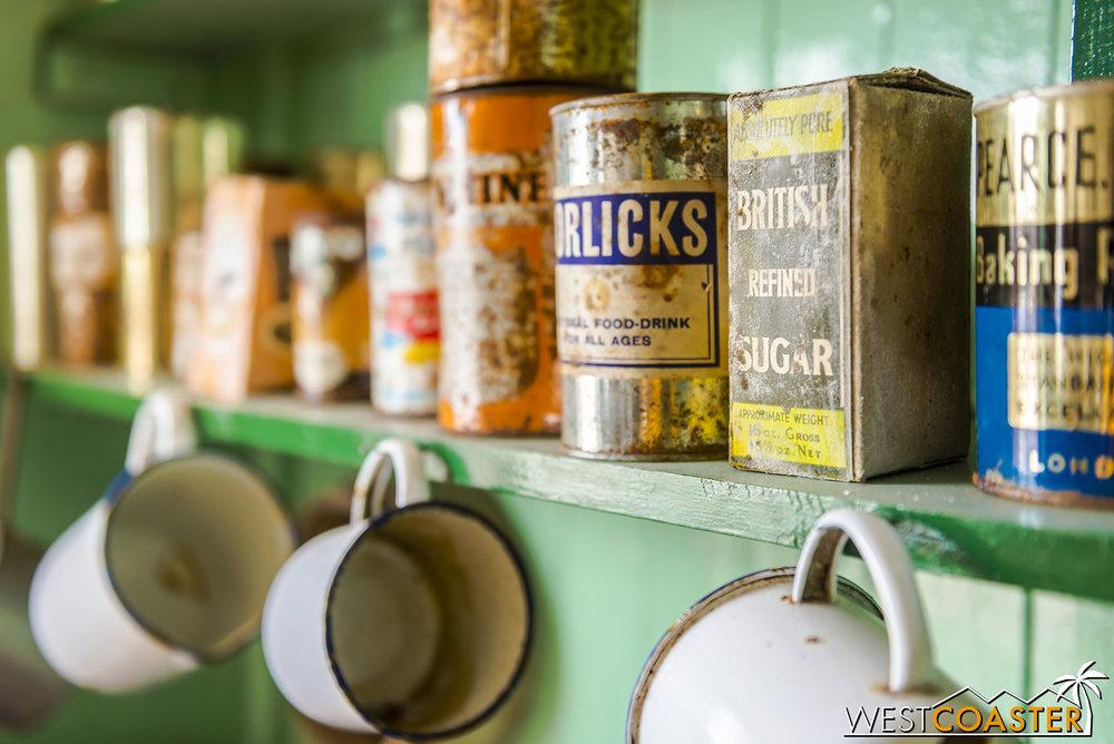 Food items and mugs on a shelf.