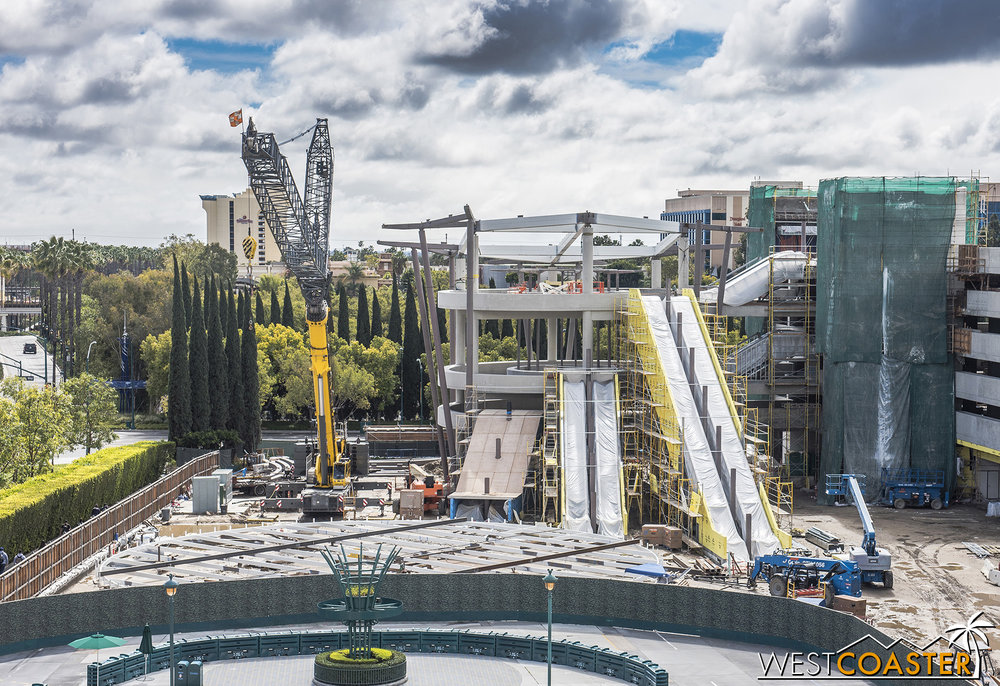 The giant, circular canopy still remains on the ground, but they've thrown up some steel beams and columns up the sides and top of the escalator promenade to support it.