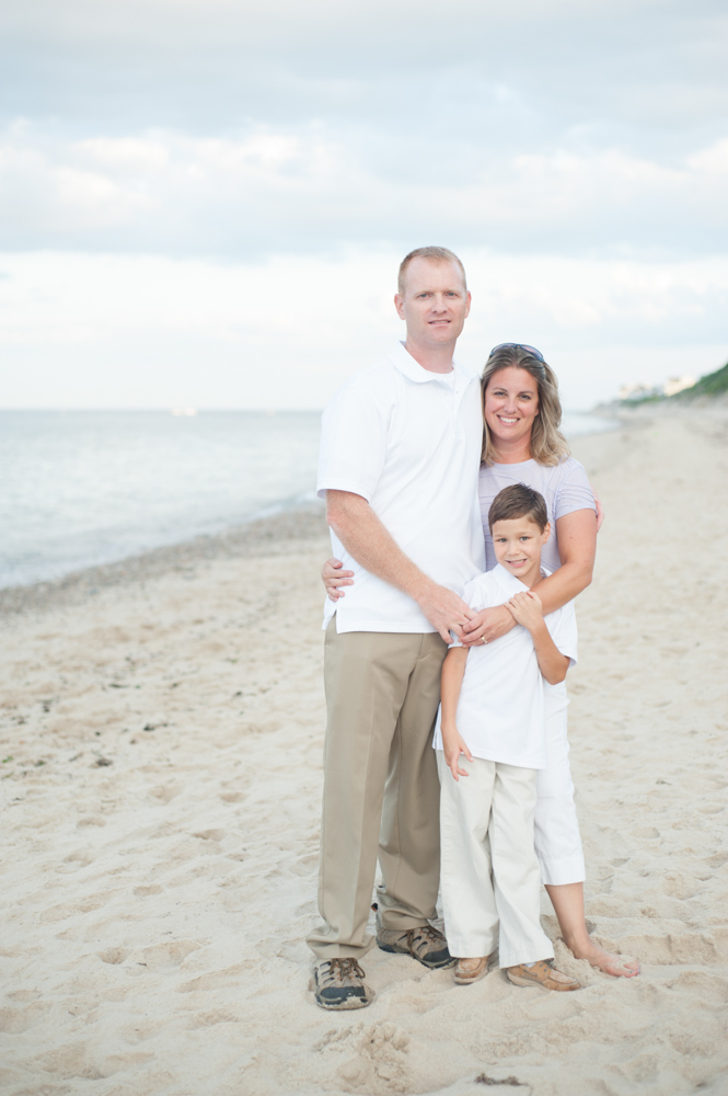 Posed family of 3 on the beach at sunset during beach portrait s