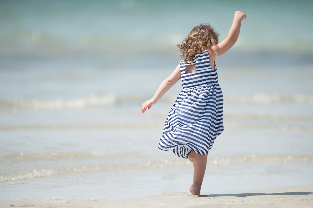 Carefree little girl dancing in the waves during family portrait