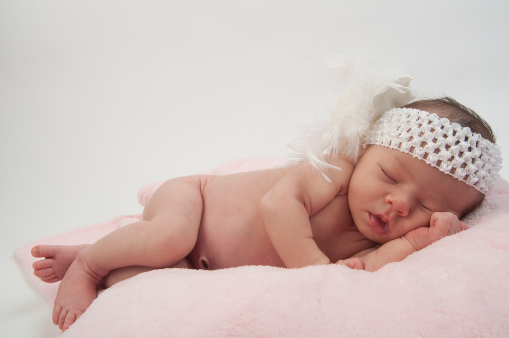 Beautiful newborn baby girl laying on a pink blanket with a feat