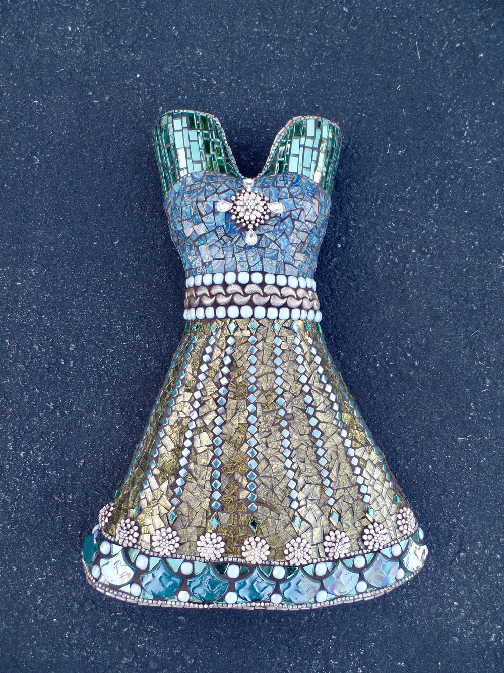 I made this mosaic dress form from sculpting wire, rigid wrap and styrofoam. The gold tone necklace at the waistband is one I purchased over 20 years ago. The blue stones/gems around the waistband and bottom border glow in the dark.I really had a difficult time deciding upon grout color. My perfection gene was surfacing so I just listened to my intuition.