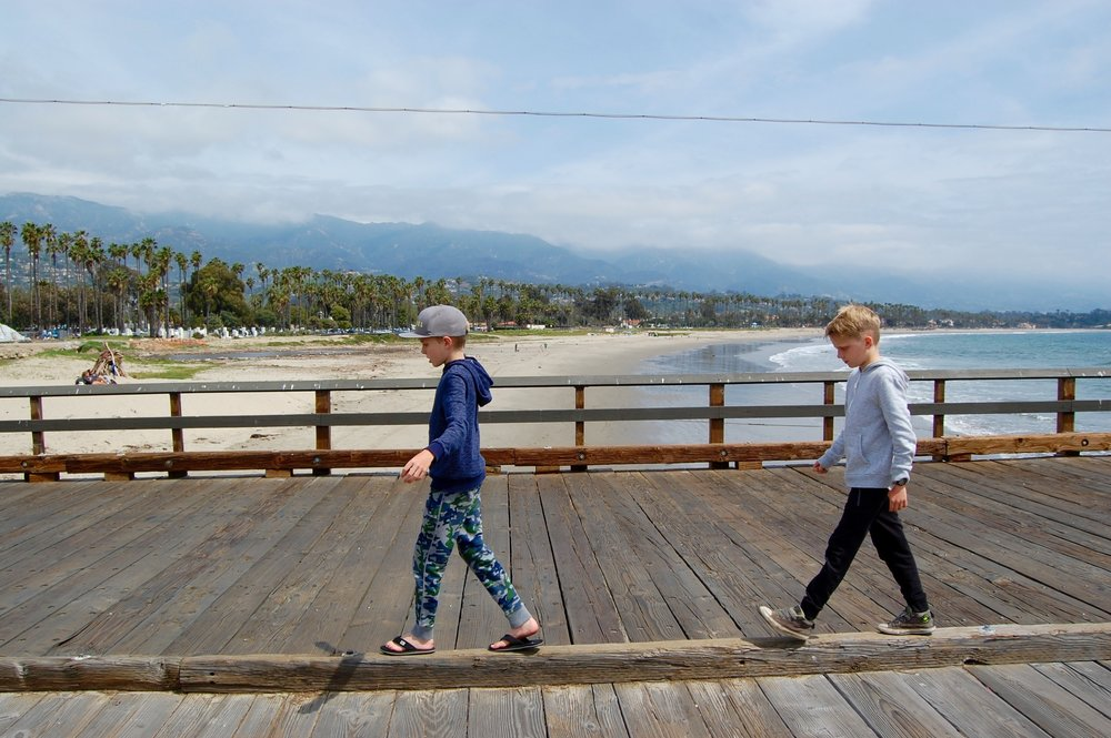 Two of my sons playing on the Santa Barbara Pier in their favorite Hanna Andersson pants: Hanna's Slim Sweats in 100% Cotton, in camouflage print and black.