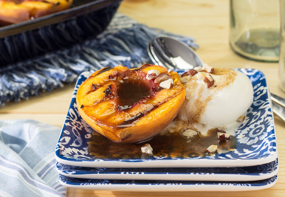 Pan grilled free stone peaches with ice cream and butter rum sauce