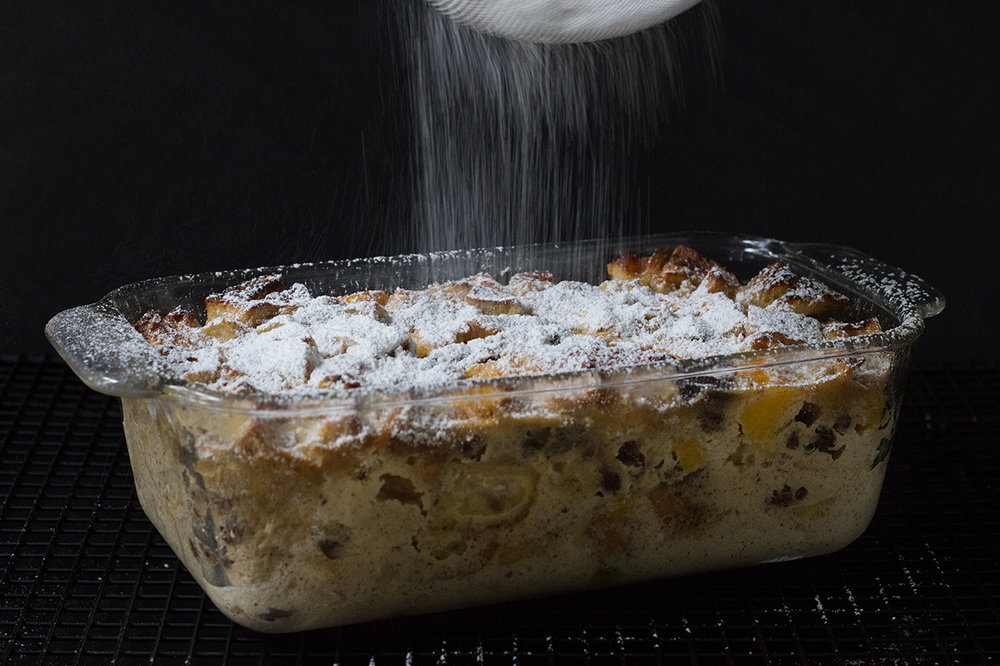 Sprinkling powdered sugar on peach raisin bread pudding