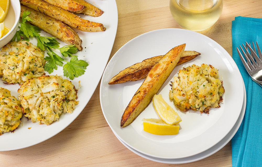 Serving crab cakes with lemon wedges and oven French fries