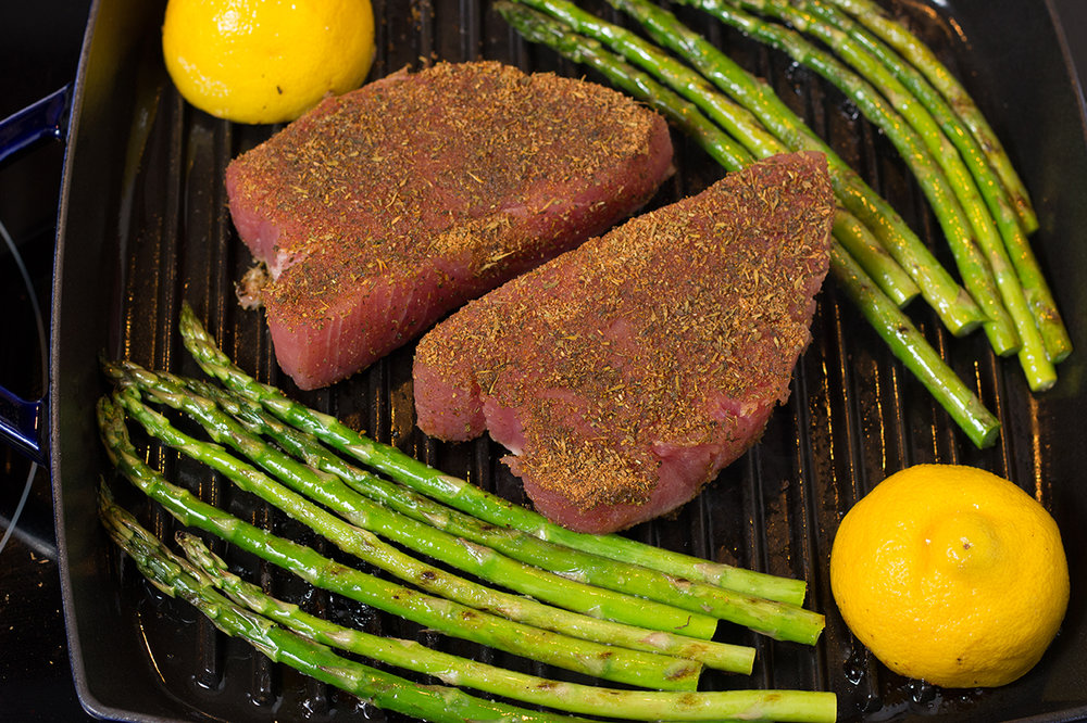 Turn over asparagus and push to sides.  Add tuna steaks to the center of the grill pan.