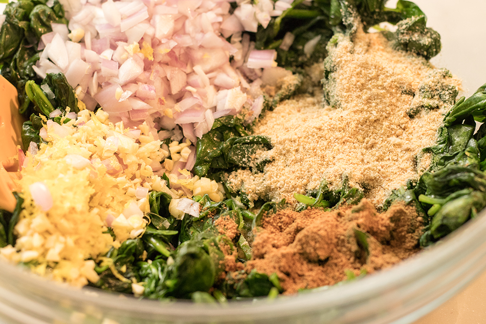 Mix in ingredients to wilted spinach.