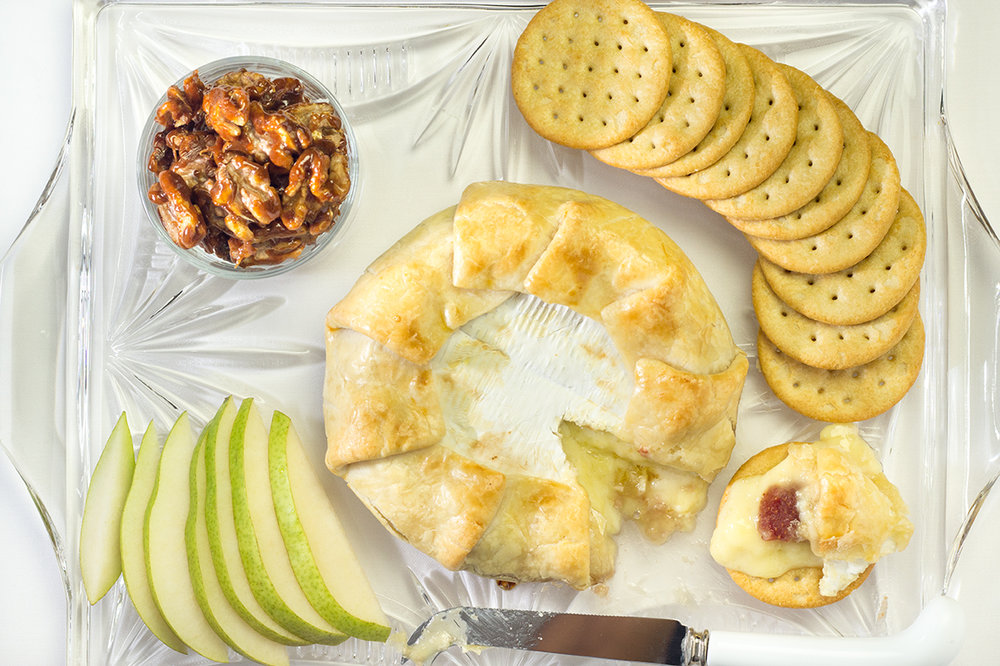 Cheeseboard with baked raspberry brie, green anjou pears, crackers and ginger sugar walnut.