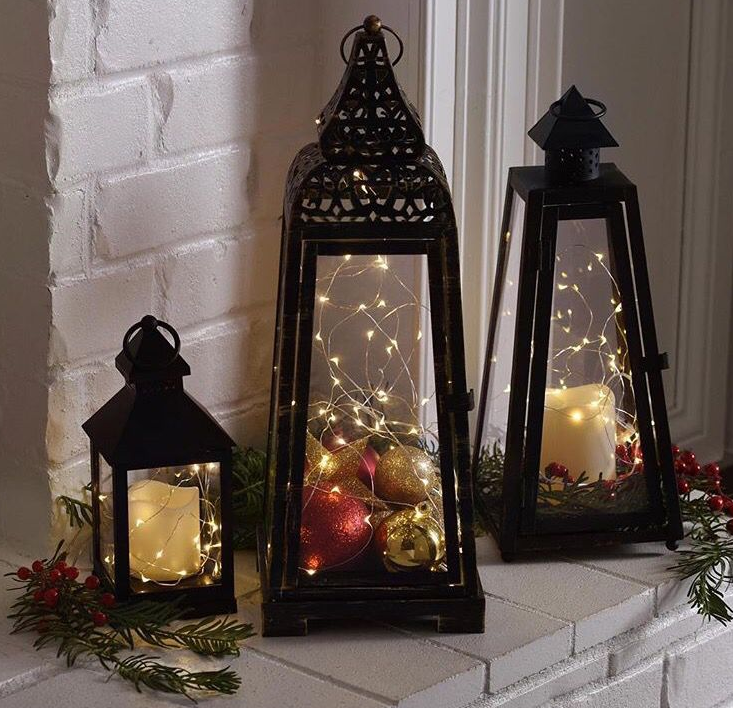 3 Hurrican lanterns with lights, candles and Christmas ornaments   source