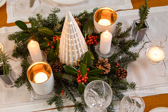 Christmas centerpiece with ceramic Christmas tree, hollies and berries, Frazer fir stems and candles.
