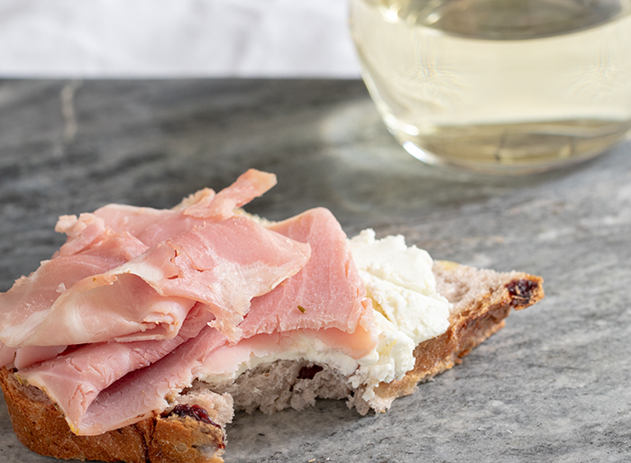 Cranberry Walnut Round Bread with Rosemary Ham and Goat Cheese with a bite taken out of it.