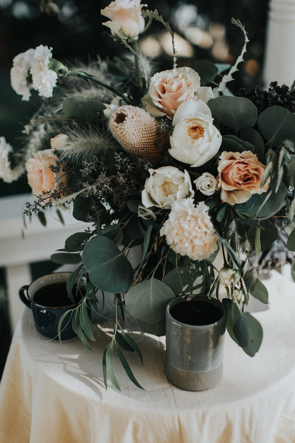 Garden roses, antique carnations, eucalyptus variations, and dried floral elements.