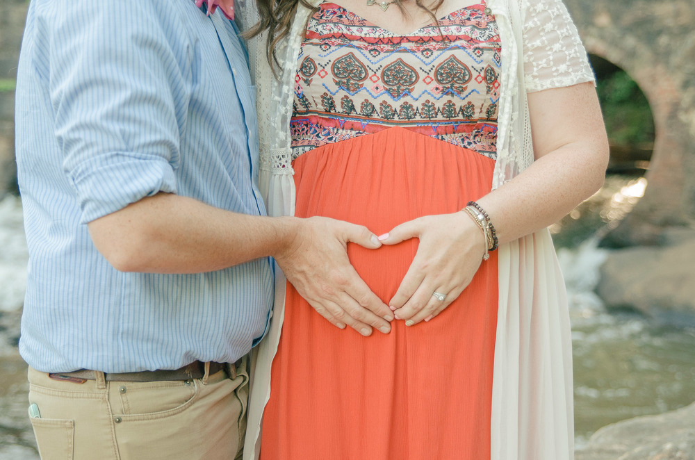 A couple placing their hands in the shape of a heart on the mother-to-be's belly