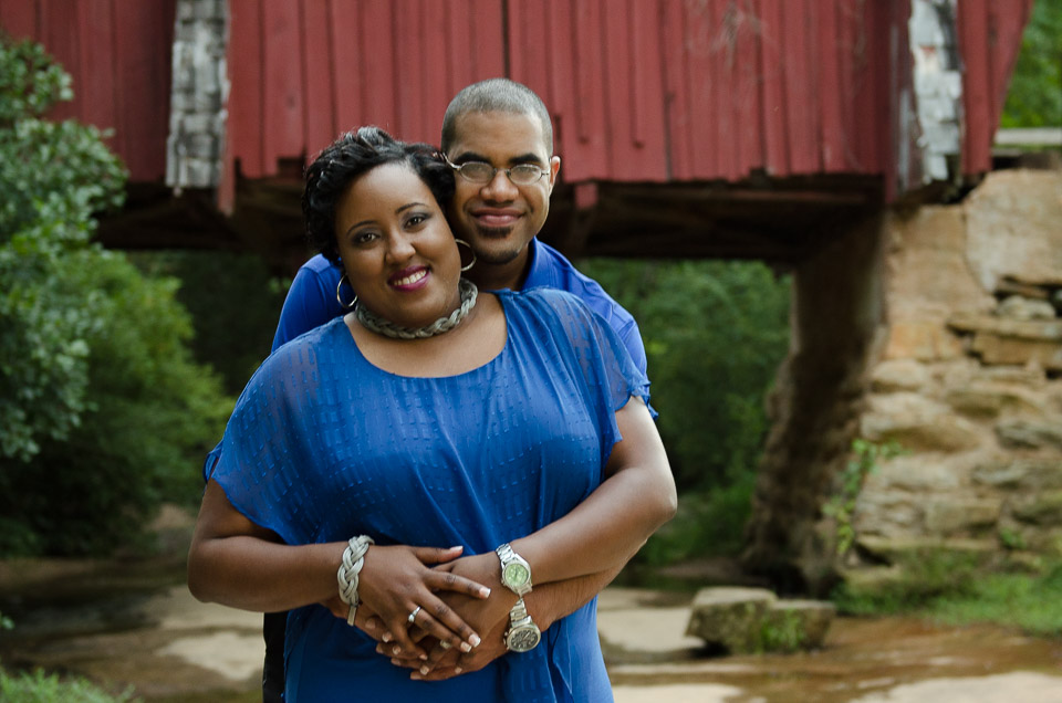 Man wraps his arms around his fiance in front of Campbell's Covered Bridge