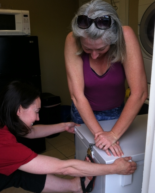 Elizabeth and Stacy installing the lock on the depot freezer located at Journey Massage.