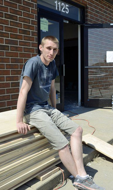 Josh Hicks sits on a stack of plywood outside the future home of The Fellow, a co-working space at 1125 Westport Drive that entrepreneurs and artists can rent as an office.