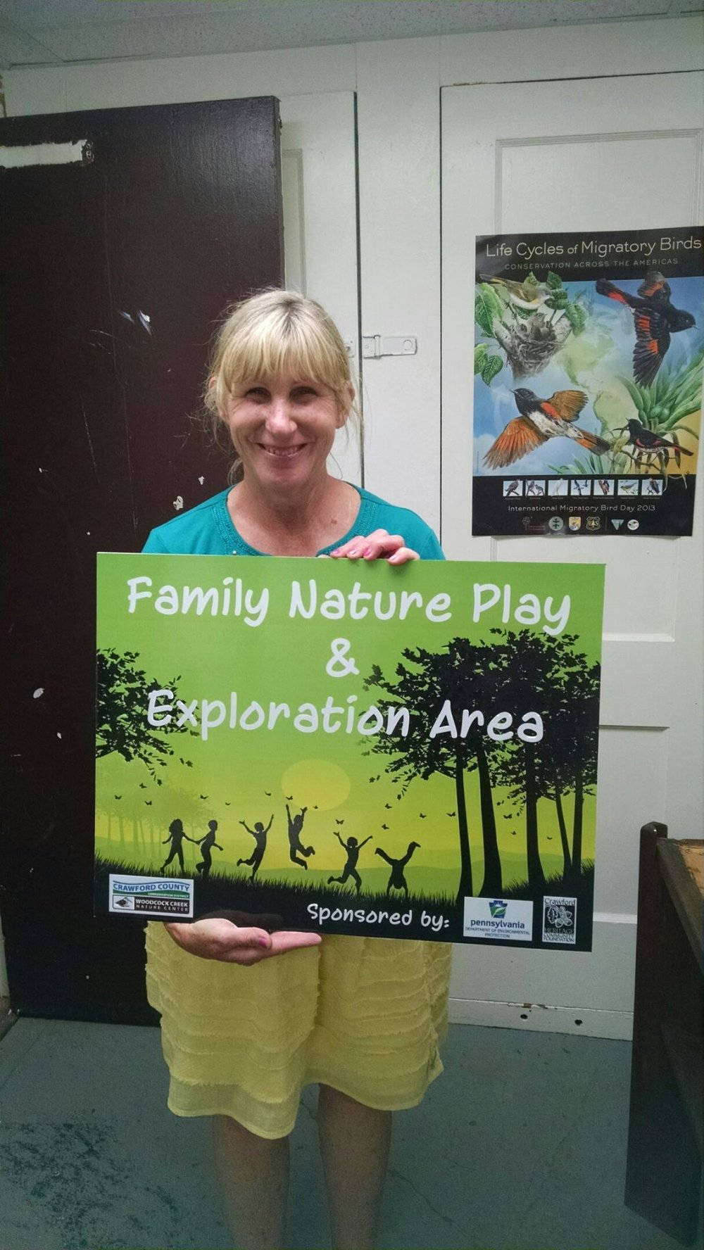 Kathy with the completed project sign. Photo taken by Kurt Kusserow summer 2016.