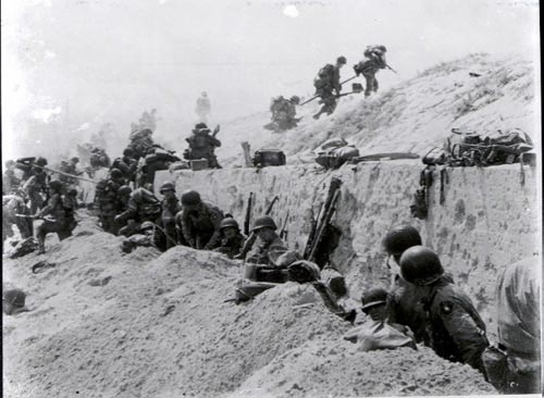 Photo by  The U.S. Army : Soldiers of the 8th Infantry Regiment, 4th Infantry Division, move over a seawall on Utah Beach during the Allied Invasion of Europe.  www.army.mil/d-day
