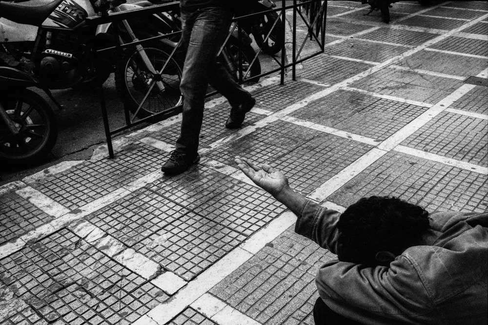 A beggar tends his hand for some spare change on Stadiou Street in central Athens