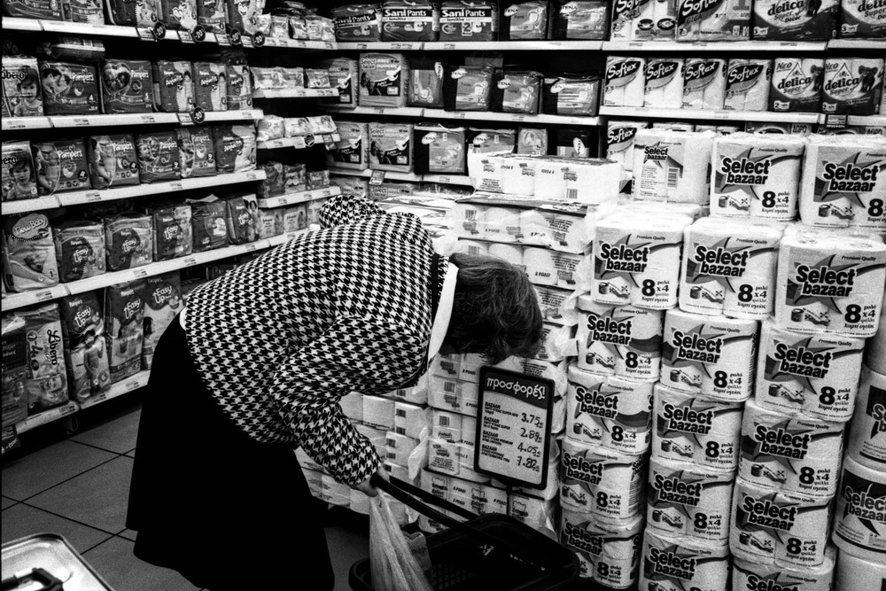A woman check the prices of toilet rolls in a mini-market in Ambelokipi area of Athens north side.