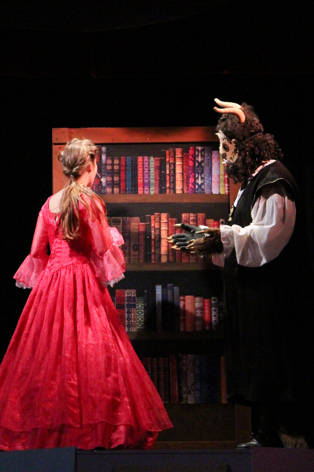 After sharing a romantic evening dance together Beast ( Remington Slater, junior ) shows Belle ( Emily Powell, senior ) his extensive library.