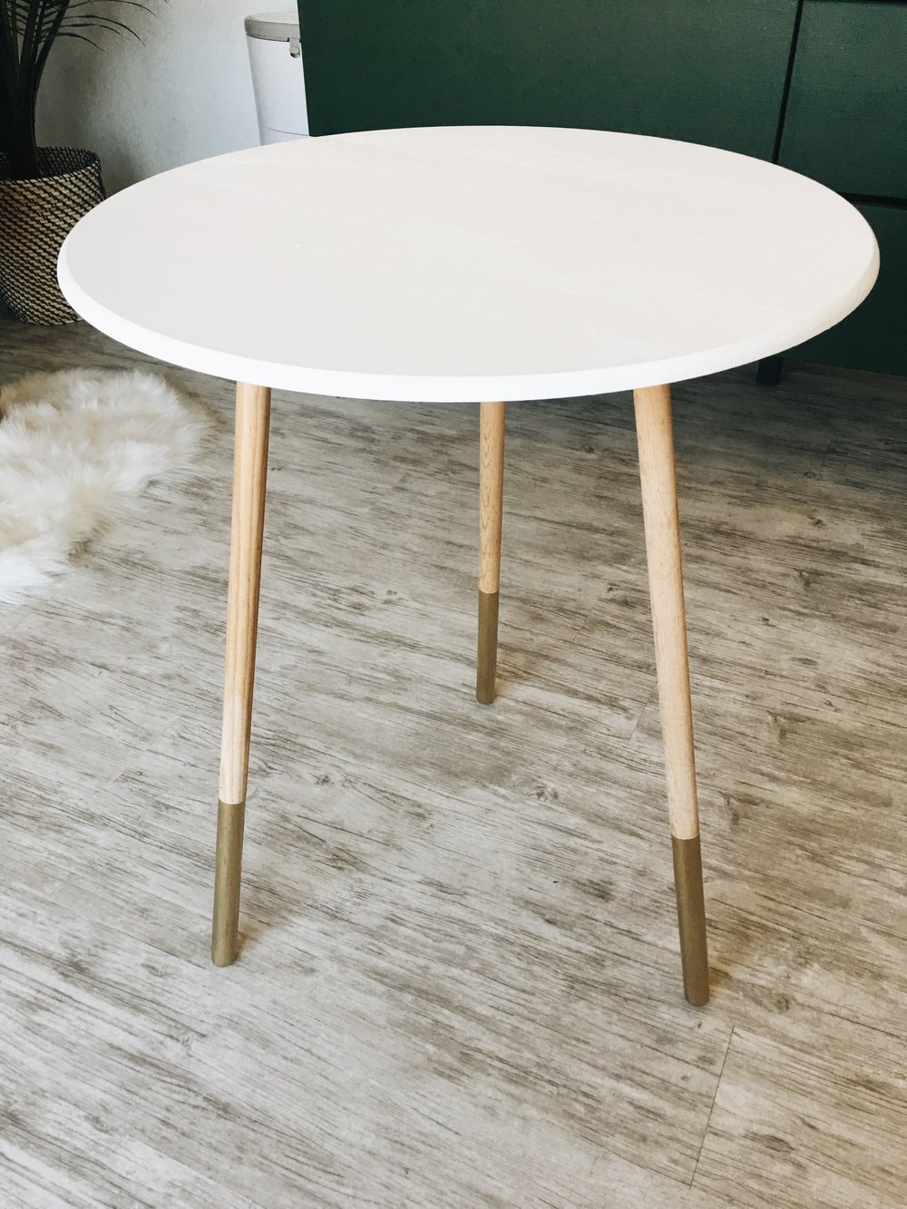 This is one of those old tables from the 80s that your mom probably had with a table cloth covering it and a glass top. We modernized it by painting the top white and adding gold to the legs.