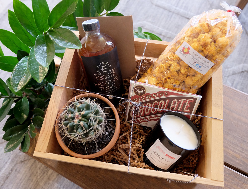 """For Him"" includes: Assorted cactus in a 4in pot, E Harlow Pristine Tonic from PourTaste, Hot & Spicy Cheddar Popcorn from Kernels Gourmet Popcorn, Mexican Style Chocolate from Olive & Sinclair, and a candle from Primary School Candles."