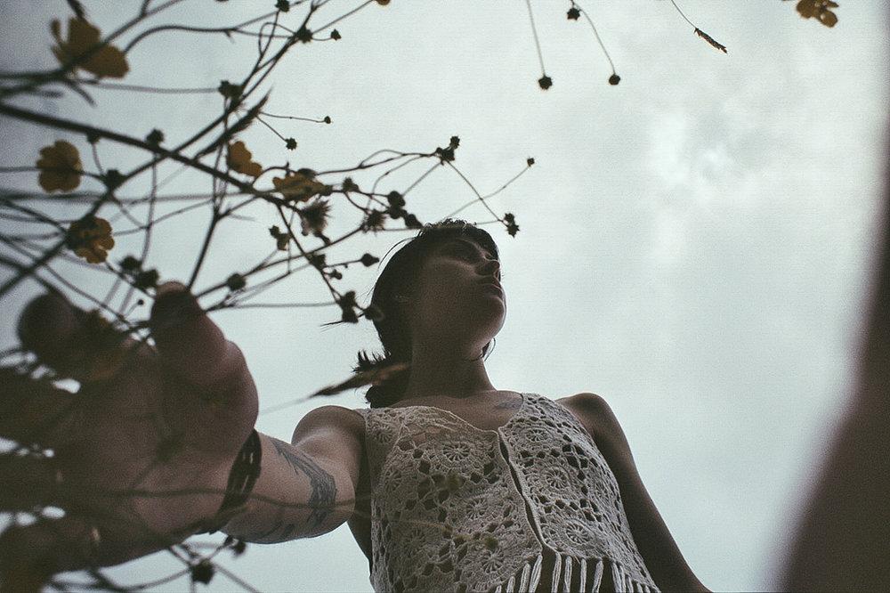 forgivenees. girl walking under cloudy sky.