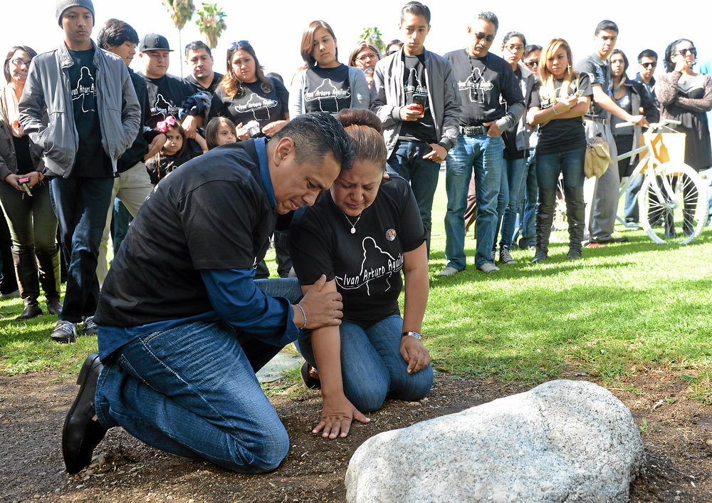 grieving parents at headstone memorial