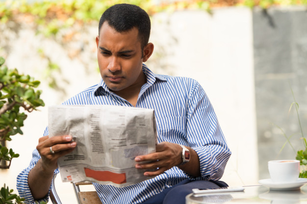 serious-man-reading-newspaper-in-outdoor-cafe_1262-6209.jpg