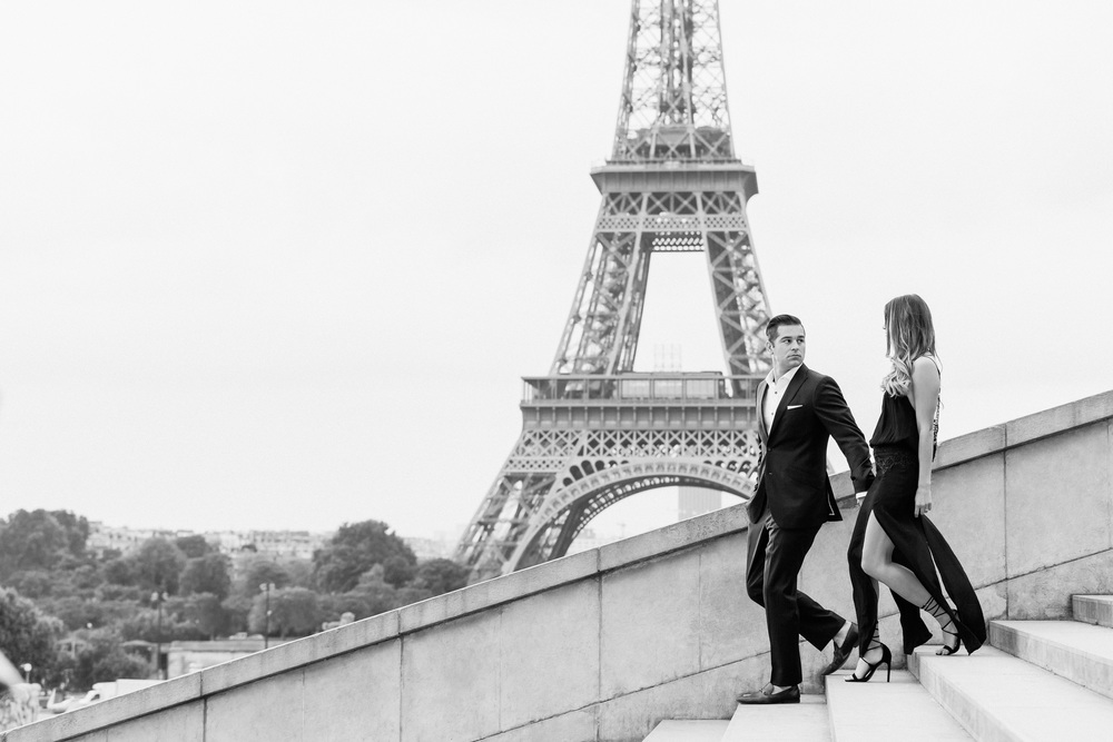 paris photographer couple walking steps of trocadero view of eiffel tower black and white