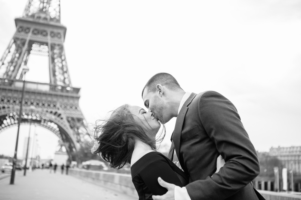 paris photographer engagement session couple kissing by the eiffel tower black and white